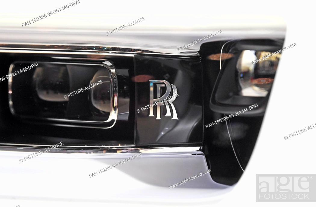 Stock Photo: 06 March 2019, Switzerland, Genf: The Rolls Royce logo can be seen in a headlight of a Rolls Royce Phantom at the Geneva Motor Show on the second press day.