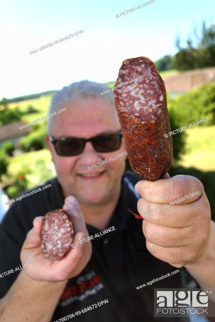 "Stock Photo: 12 June 2020, Bavaria, Dachsbach: Günther Schlegel, butcher, presents a salami made with Franconian wine (to dpa: """"Sausage."