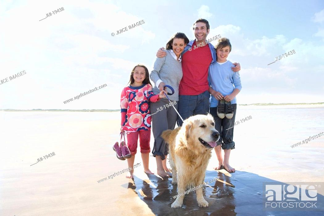 Stock Photo: Family with dog on beach.