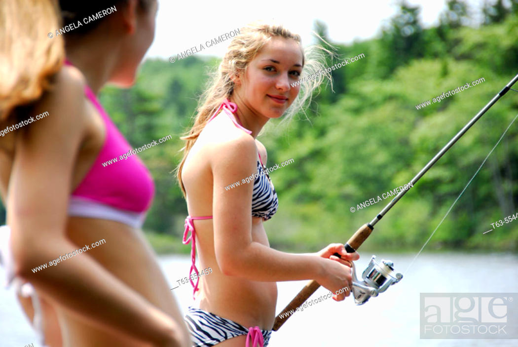 Stock Photo: girl 18 looking at girl 13 fishing on dock at cottage.