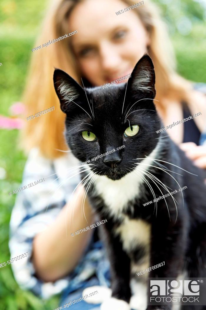 Stock Photo: Portrait of a cat with smiling young woman in the background.