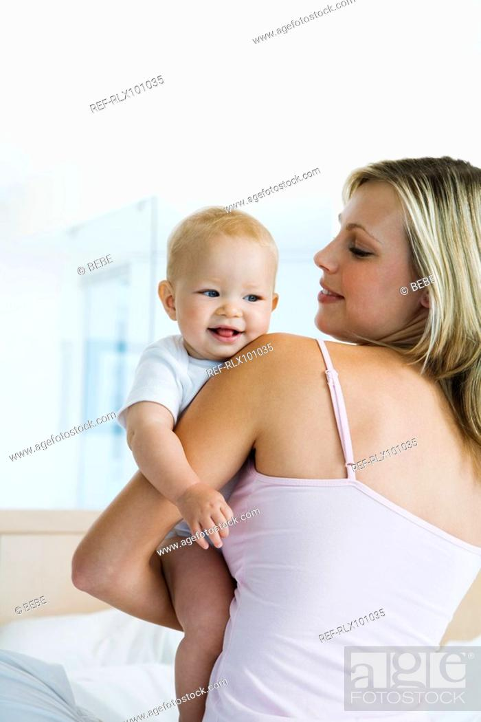Stock Photo: Young mother holding baby 6-12 months in bedroom, baby looking over shoulder.