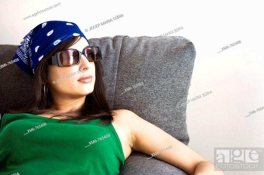 Stock Photo: Girl sitting on the couch by the window looking pensive.
