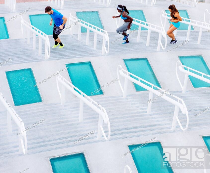 Stock Photo: Man and two women training, stepping sideways on stairway at sport facility, downtown San Diego, California, USA.