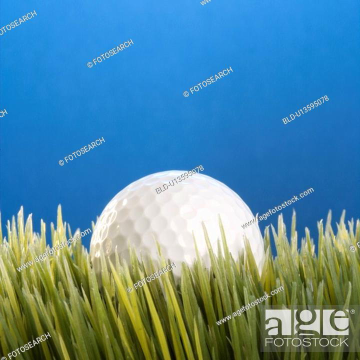 Stock Photo: Studio shot of a golf ball resting in grass.
