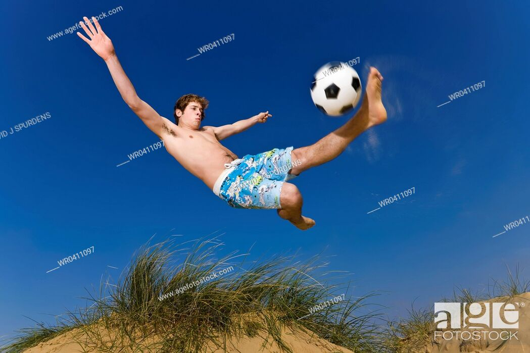 Stock Photo: A beach soccer player takes a flying volley.