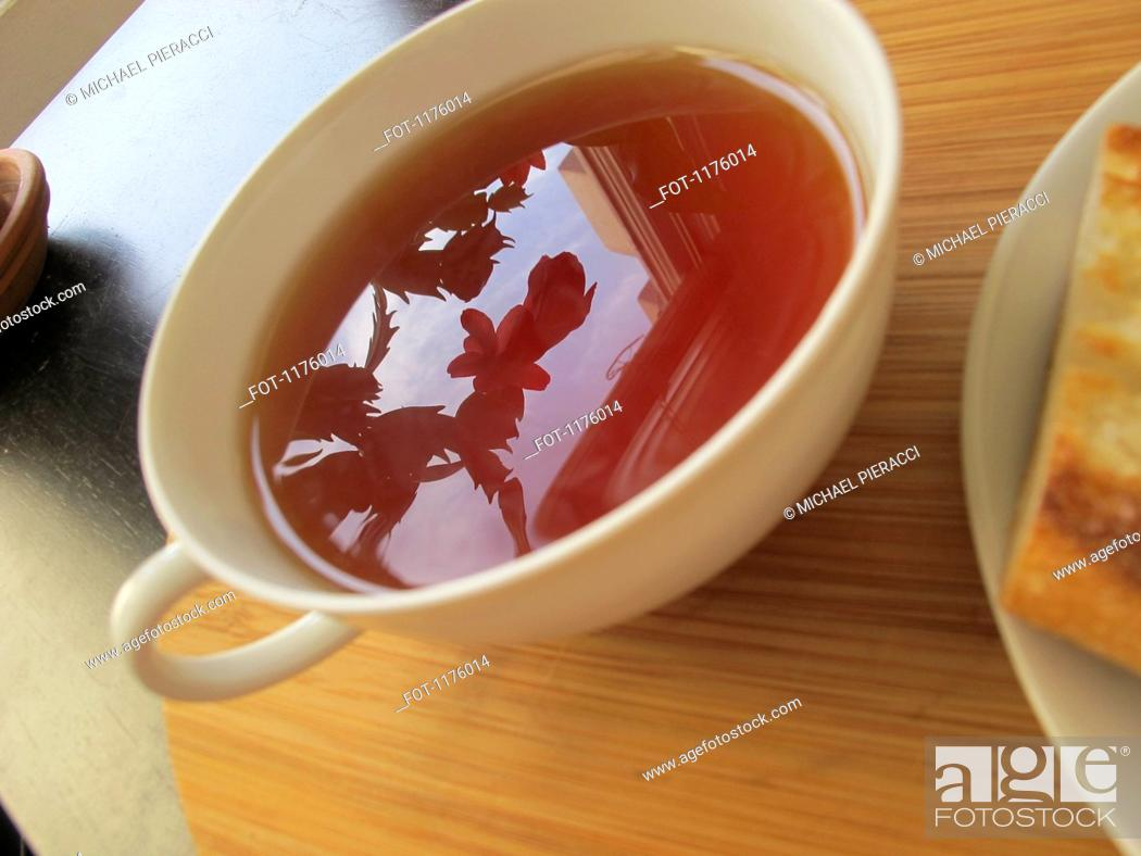 Stock Photo: Plant, sky and building reflected in tea.