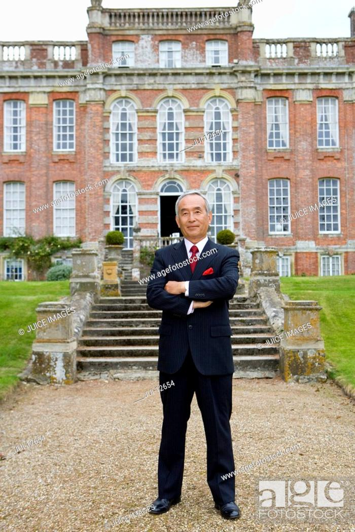 Stock Photo: Mature businessman with arms crossed in front of manor house, portrait.