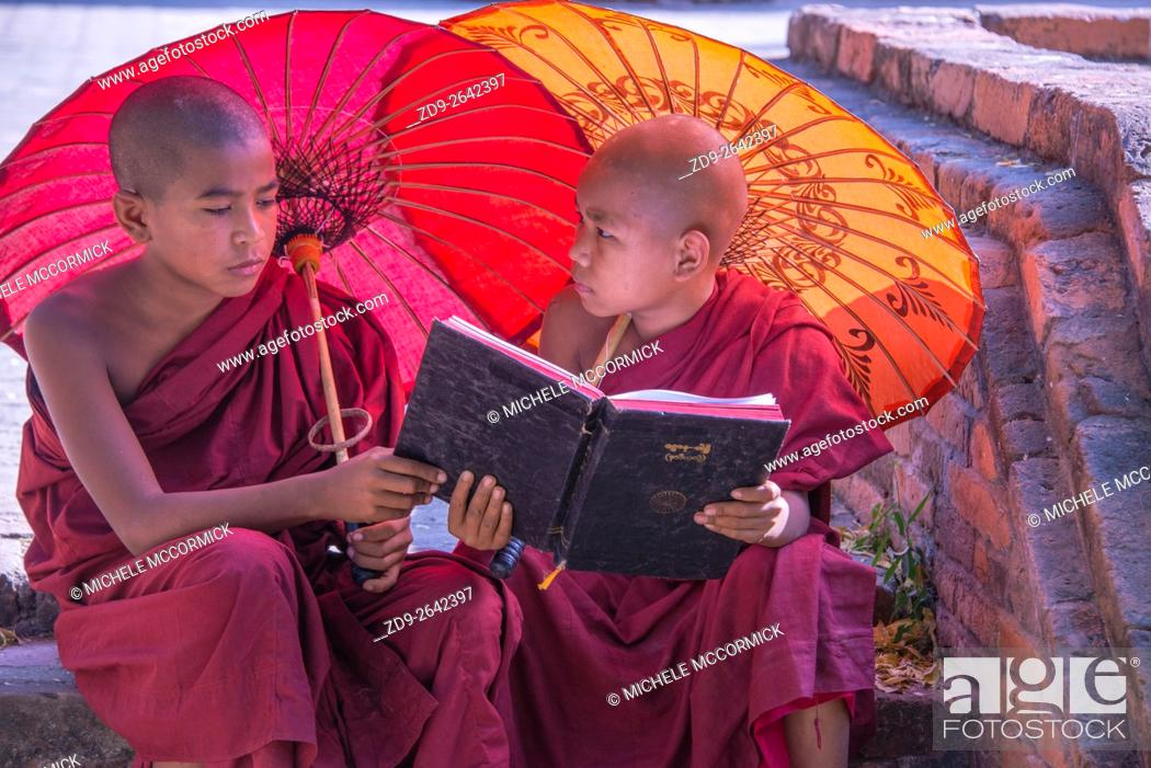 Stock Photo: Two young monks study outside Bagan's Sularmuni Temple.