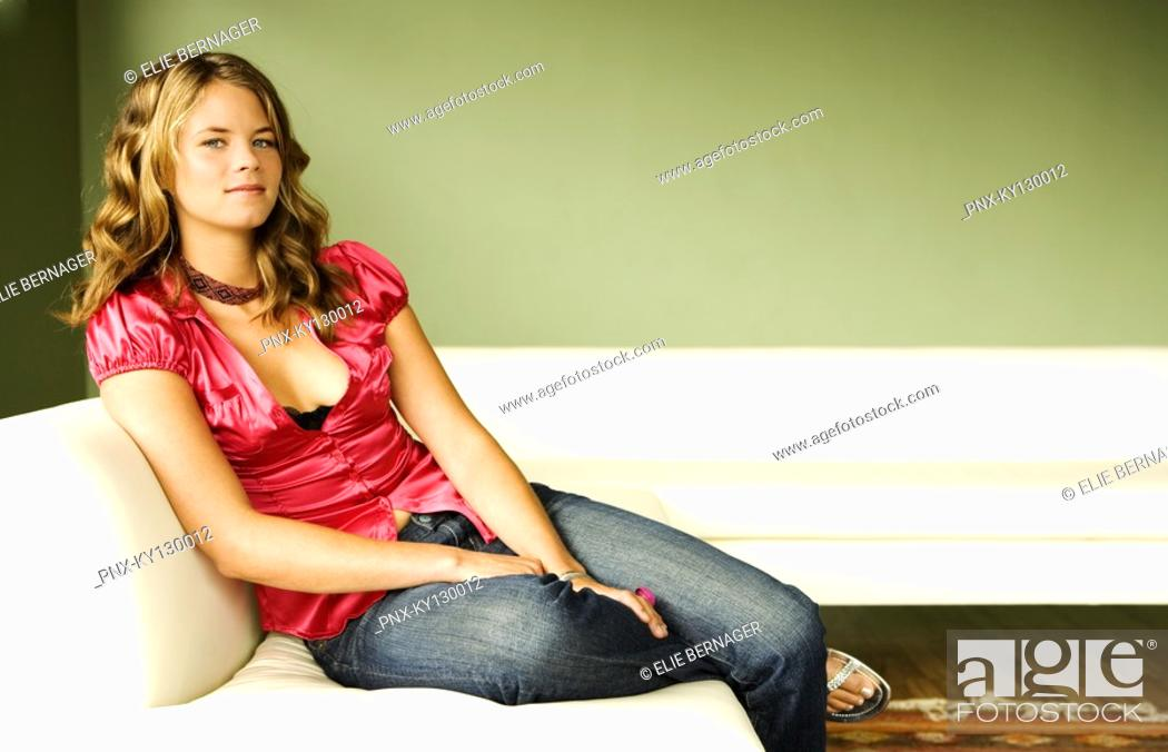 Stock Photo: Young woman sitting on a sofa.