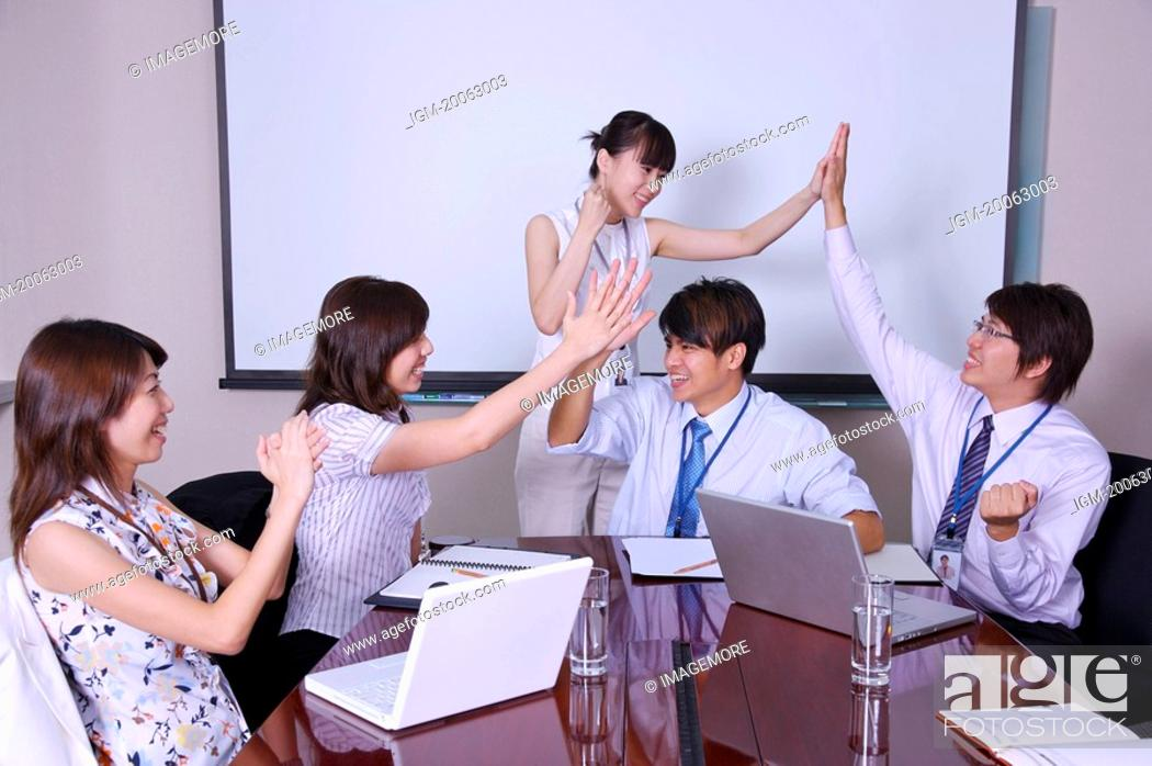 Stock Photo: Colleagues making high-five together to celebrate success.