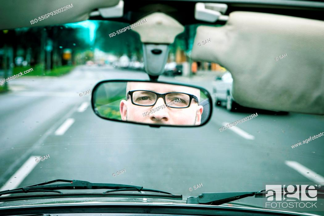 Stock Photo: Reflection of young man wearing glasses driving car in rearview mirror.