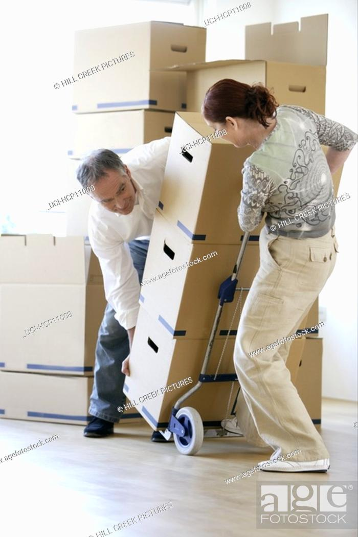 Stock Photo: Couple moving stacked boxes.