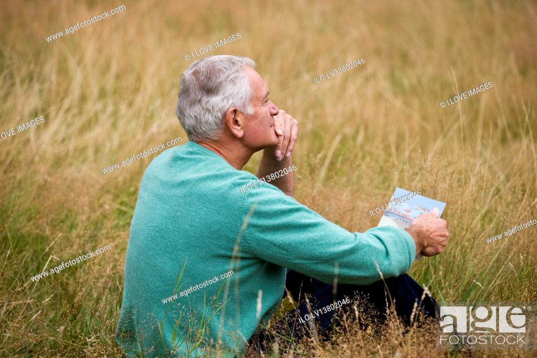 Stock Photo: A senior man sitting on the grass, holding a book, looking thoughtful.