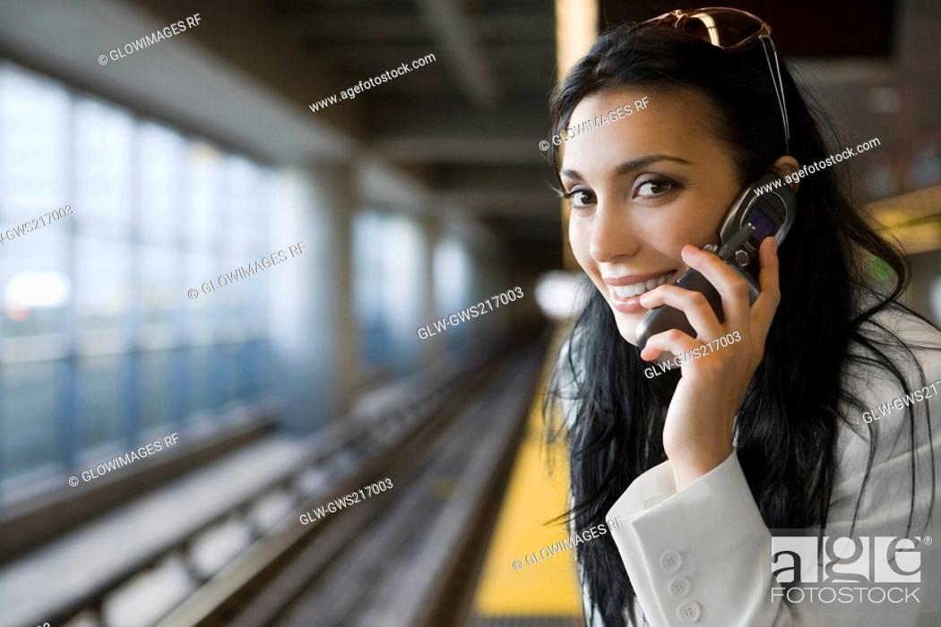 Stock Photo: Portrait of a young woman talking on a mobile phone at a subway station.