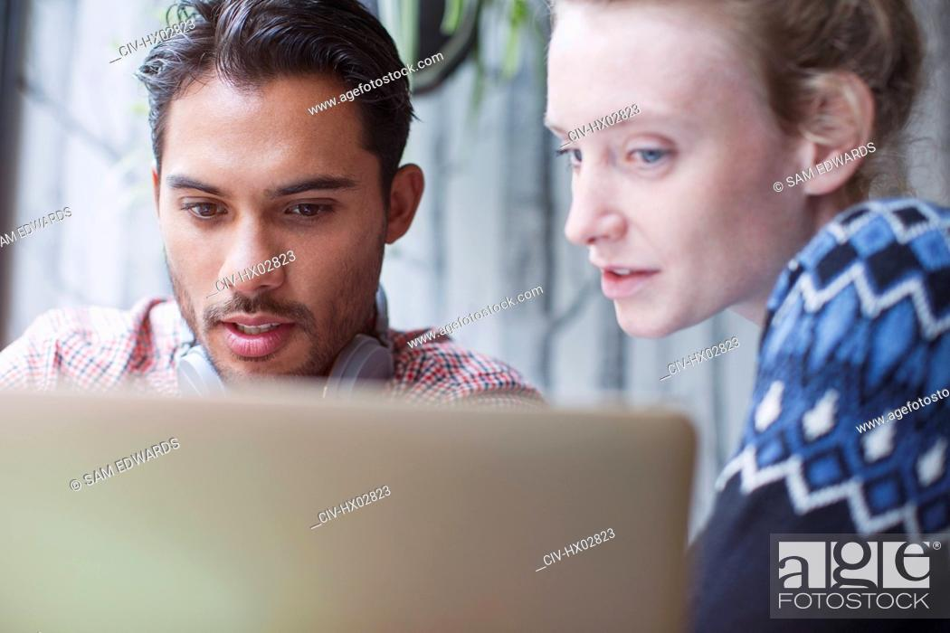 Stock Photo: Serious young man and woman using laptop in cafe.