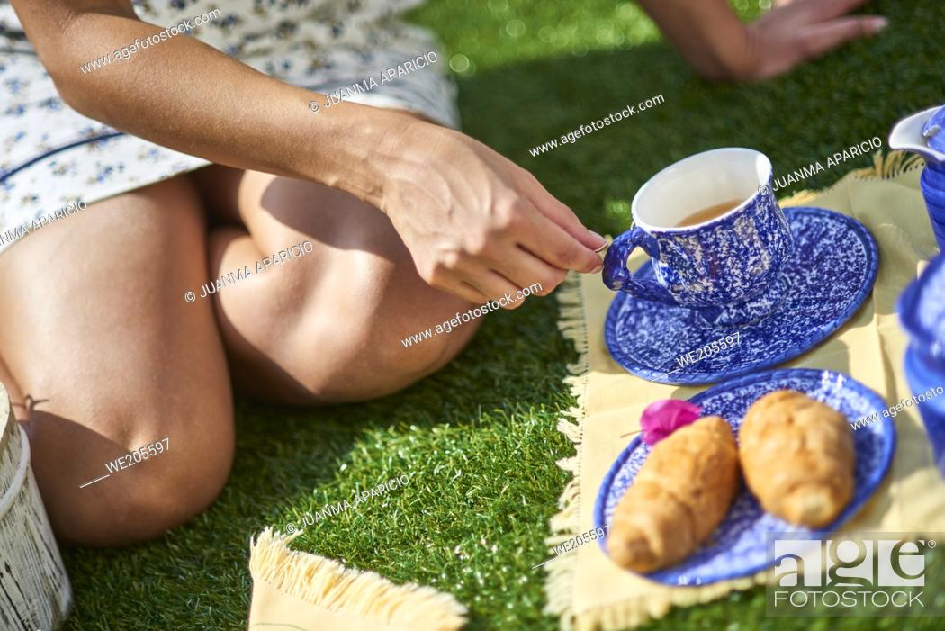 Stock Photo: Detail of woman sitting on the grass with cup of tea in the picnic.