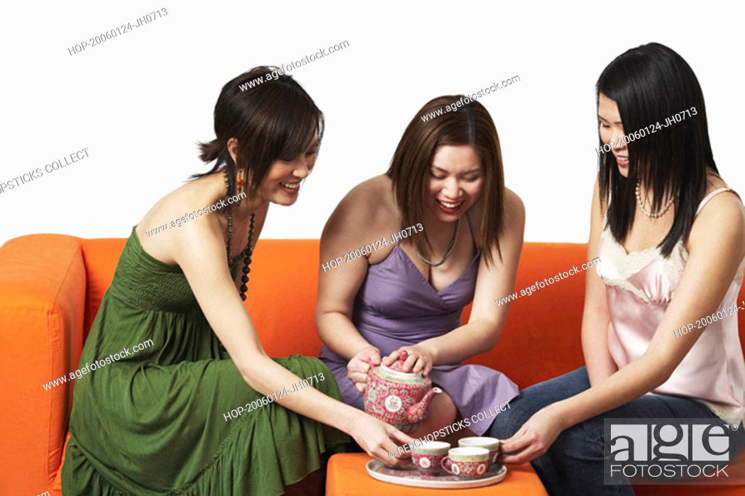 Stock Photo: Three young women sitting on a couch with tea cups.