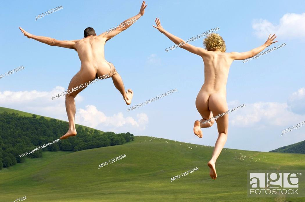 Stock Photo: Young naked couple running and jumping in mountain field back view.