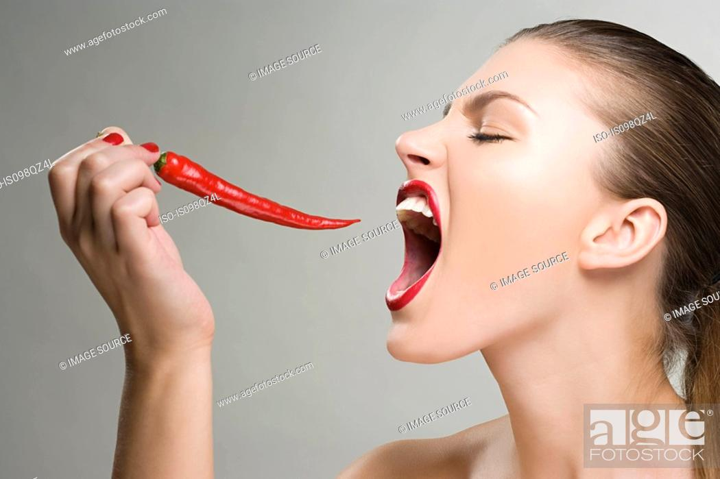 Stock Photo: Woman biting a red chili pepper.