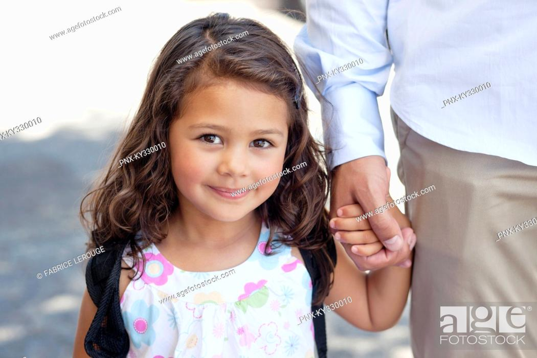 Stock Photo: Portrait of a little girl holding her father's hand.