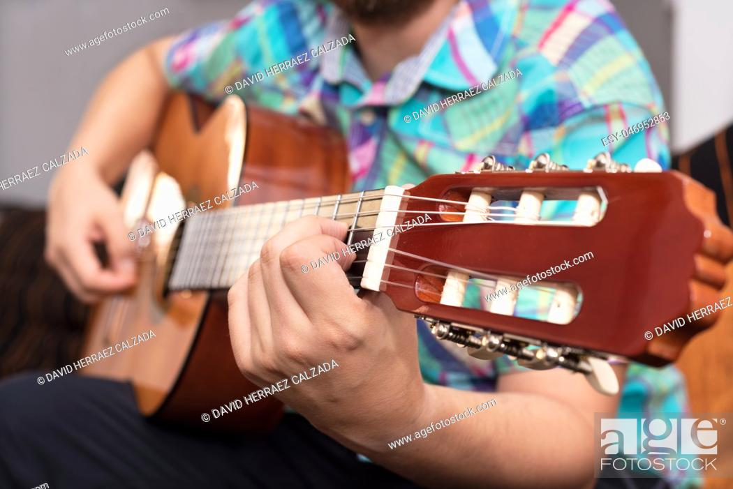Imagen: Bearded hipster man hand playing acoustic guitar. Close-up selective focus on hand.