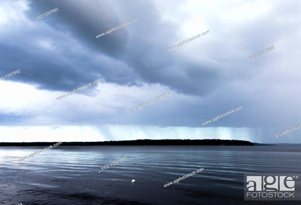 Stock Photo: Rain and heavy clouds over lake, Sweden.