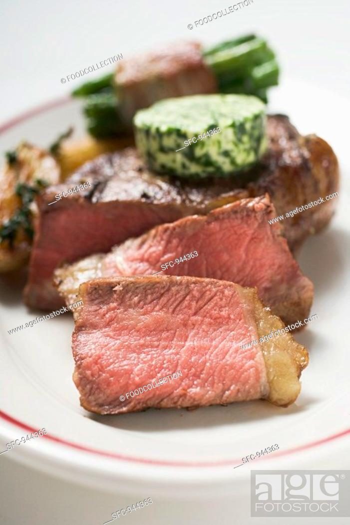 Stock Photo: Beef steak with herb butter and bacon-wrapped beans.