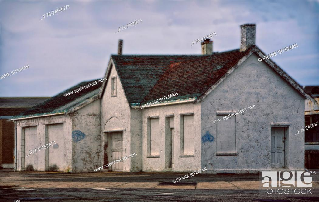 Stock Photo: Abandoned and boarded-up building on Mass Ave in Arlington, MA which was once a gas station and is now just painted white. USA.