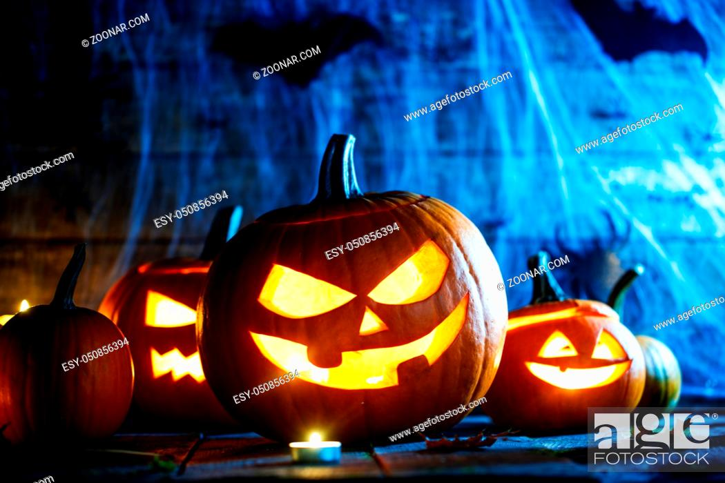 Stock Photo: Jack O Lantern Halloween pumpkins, spiders on web, bats and burning candles.