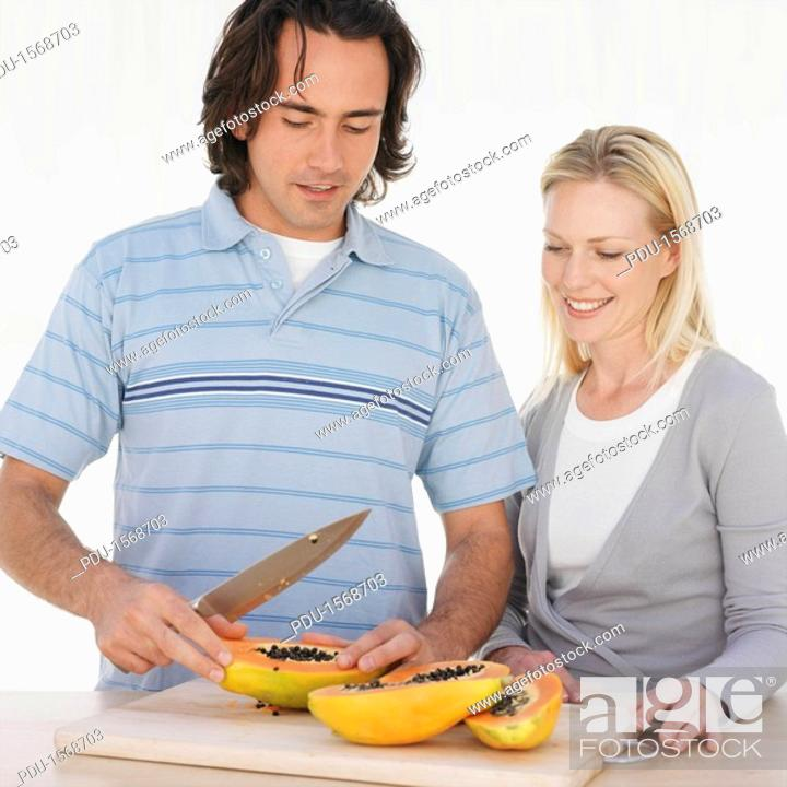 Stock Photo: Couple slicing fruit in kitchen.