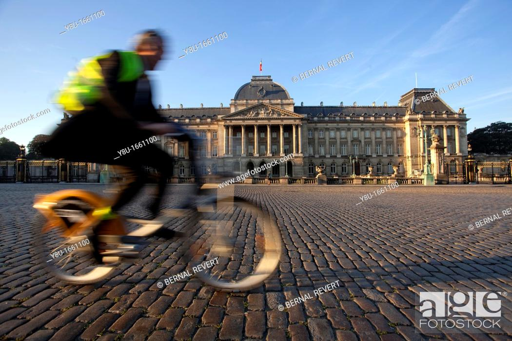 Stock Photo: A man rides a bike next to the Royal Palace in Brussels, Belgium.