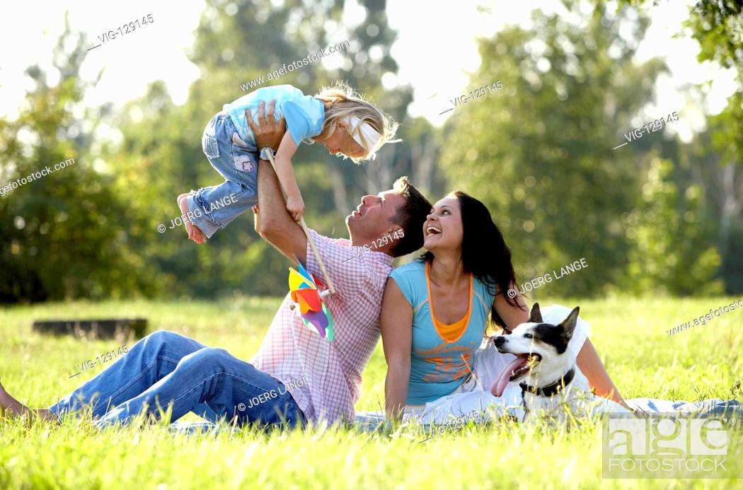 Stock Photo: A young family seeking relaxation in a park.  - Dresden, GERMANY, 05/09/2005.