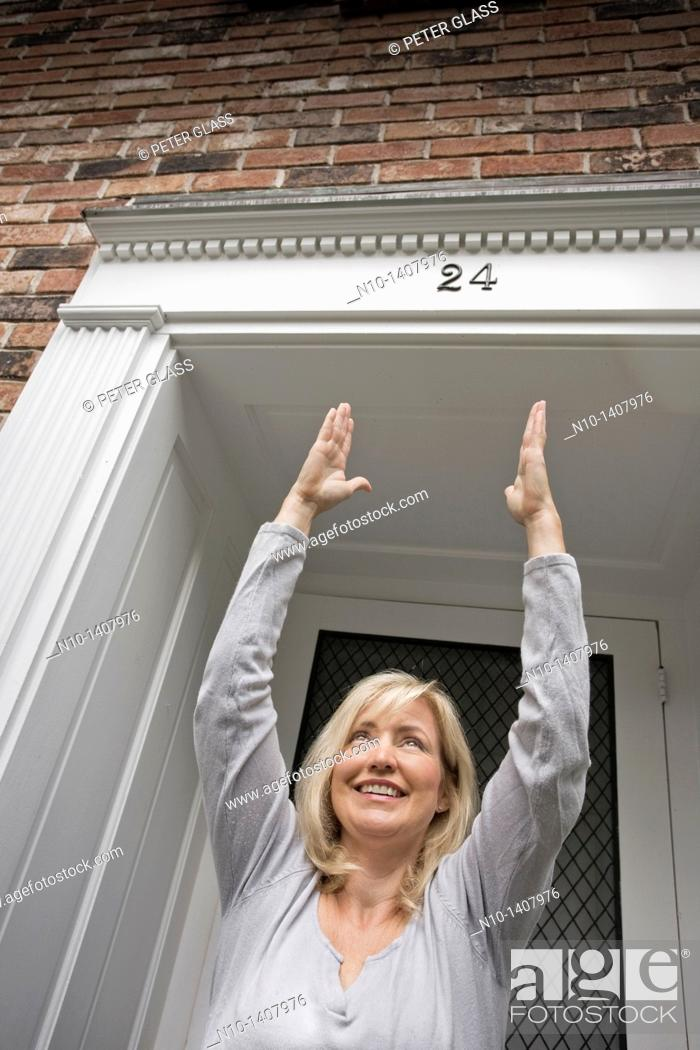 Stock Photo: Middle-age blond woman standing by her front door.