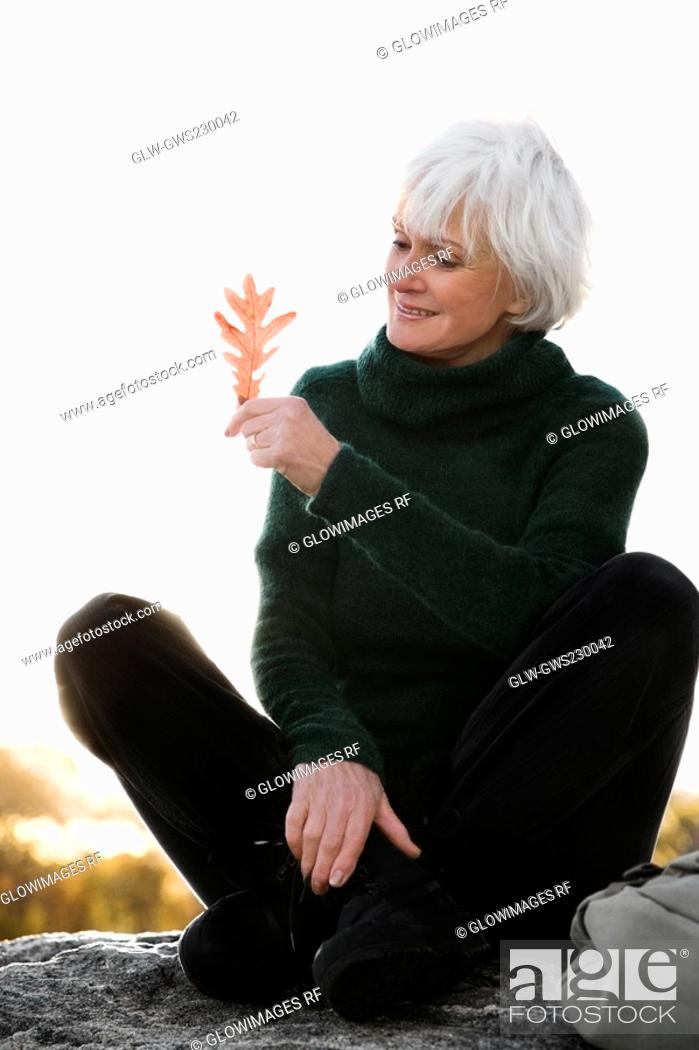 Stock Photo: Senior woman sitting on a rock and looking at a leaf.