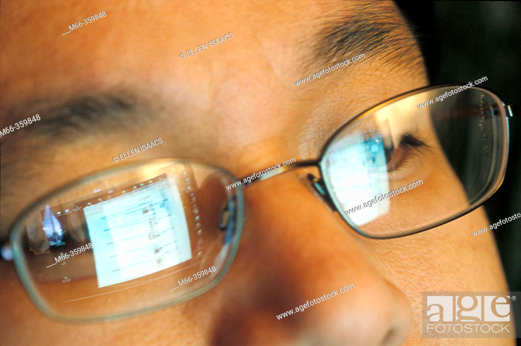 Stock Photo: Laptop screen reflecting in an Asian-American man's glasses as he surfs the Internet.