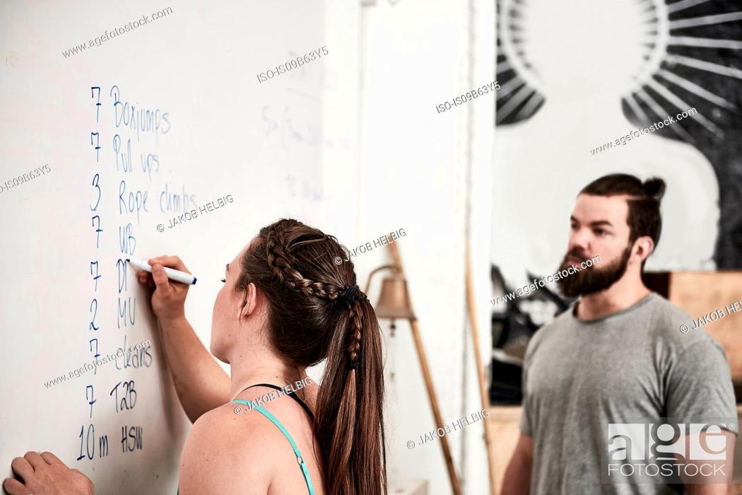 Stock Photo: Fitness instructor writing on whiteboard in cross training gym.