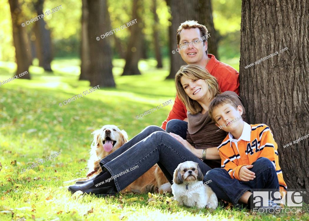 Stock Photo: Happy young family posing in front of the camera with Golden Retriever and Shih Tzu dogs.