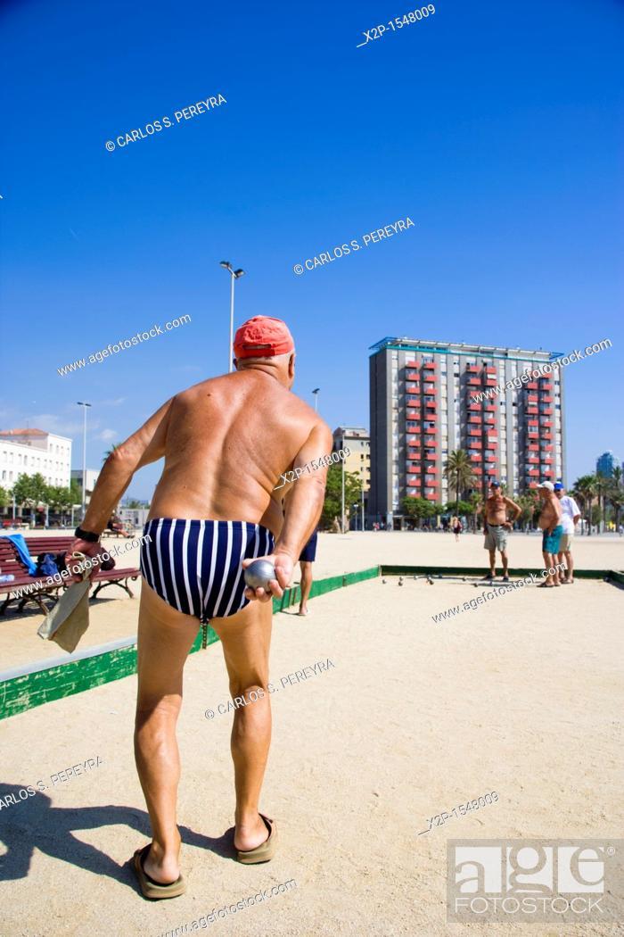 Stock Photo: Group of men playing petanca in Barceloneta Beach, Barcelona, Spain.