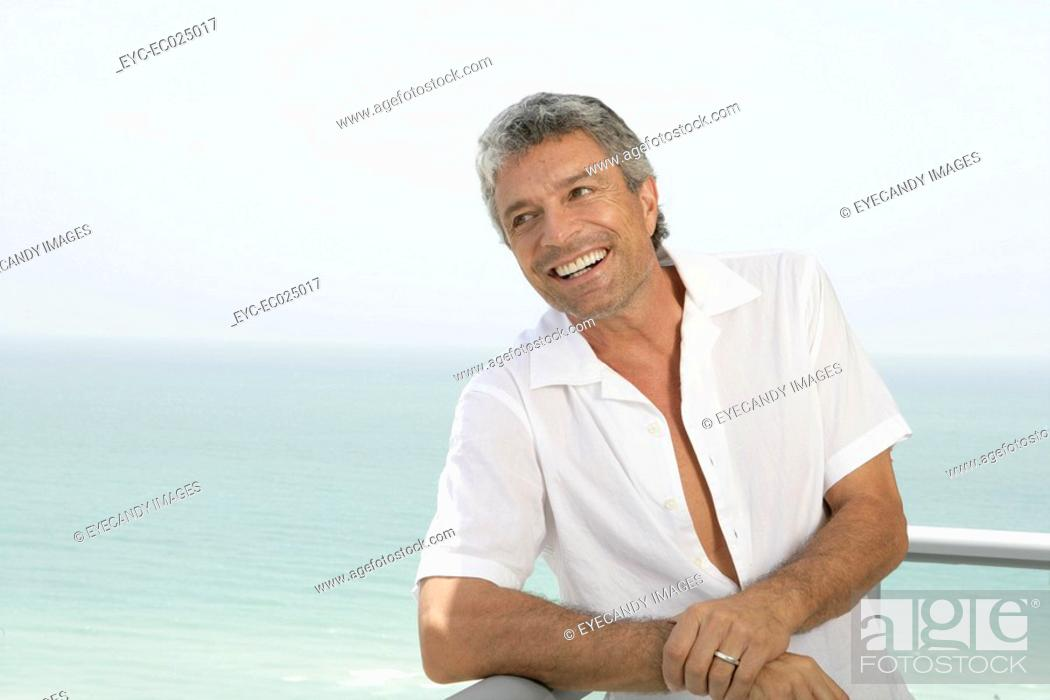 Stock Photo: Mature married man smiling on a terrace.