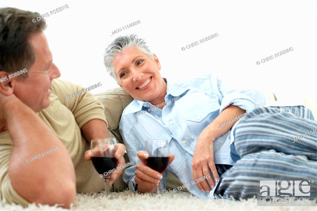 Stock Photo: Couple drinking wine on rug in home.