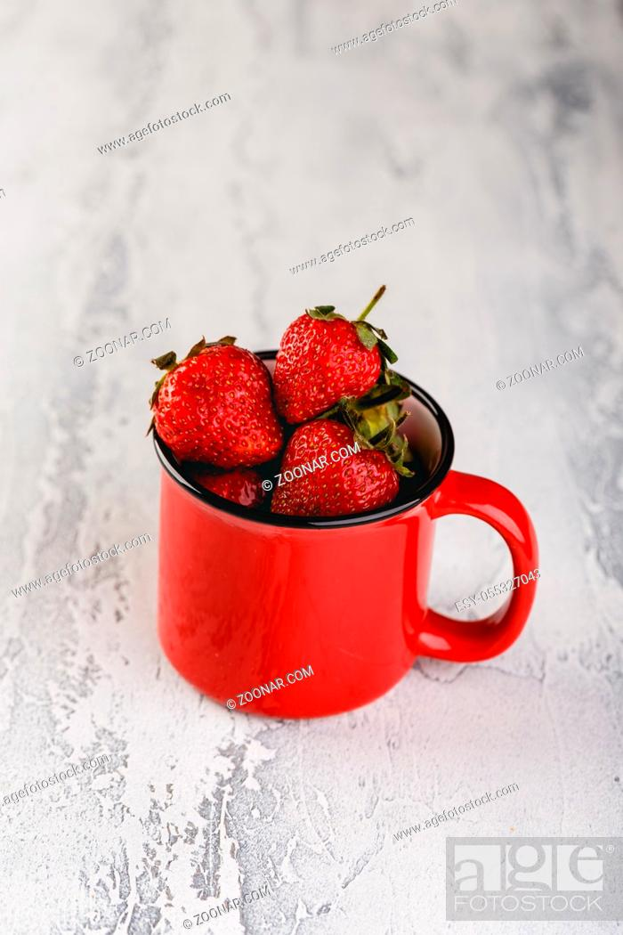 Stock Photo: Fresh Strawberries in red enamel cup on grey background.