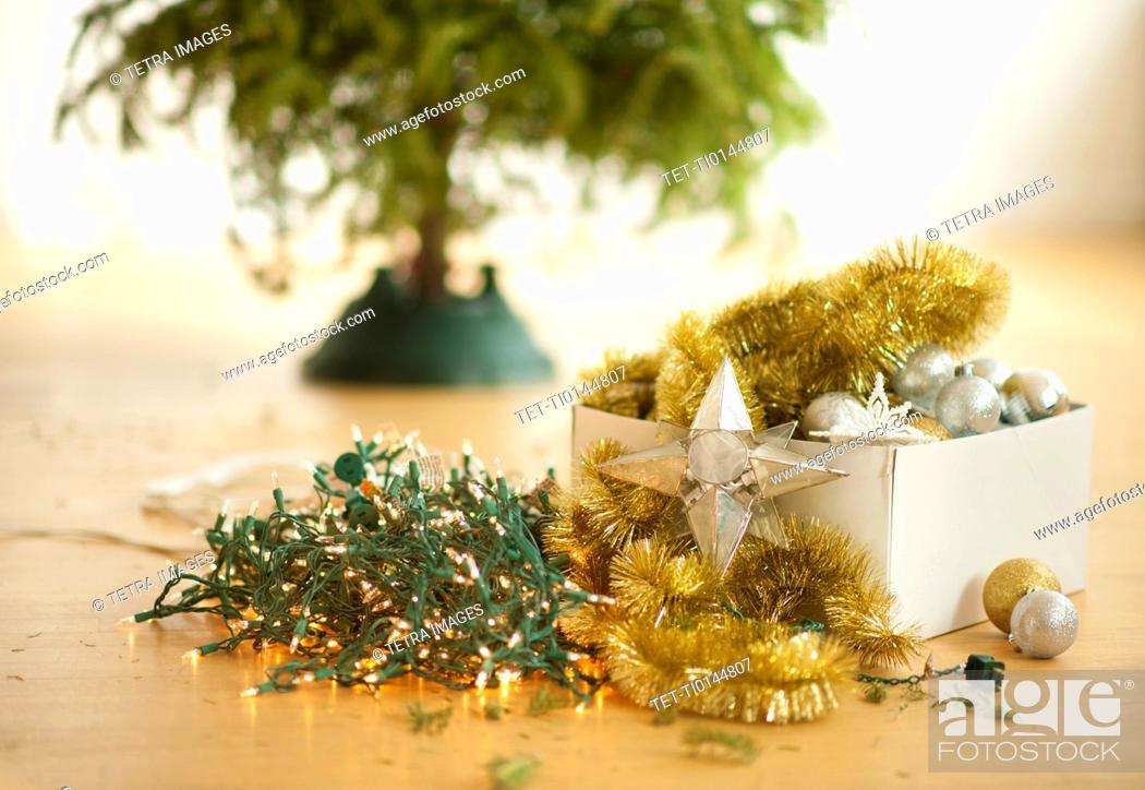 Stock Photo: Christmas tree and christmas ornaments on floor.
