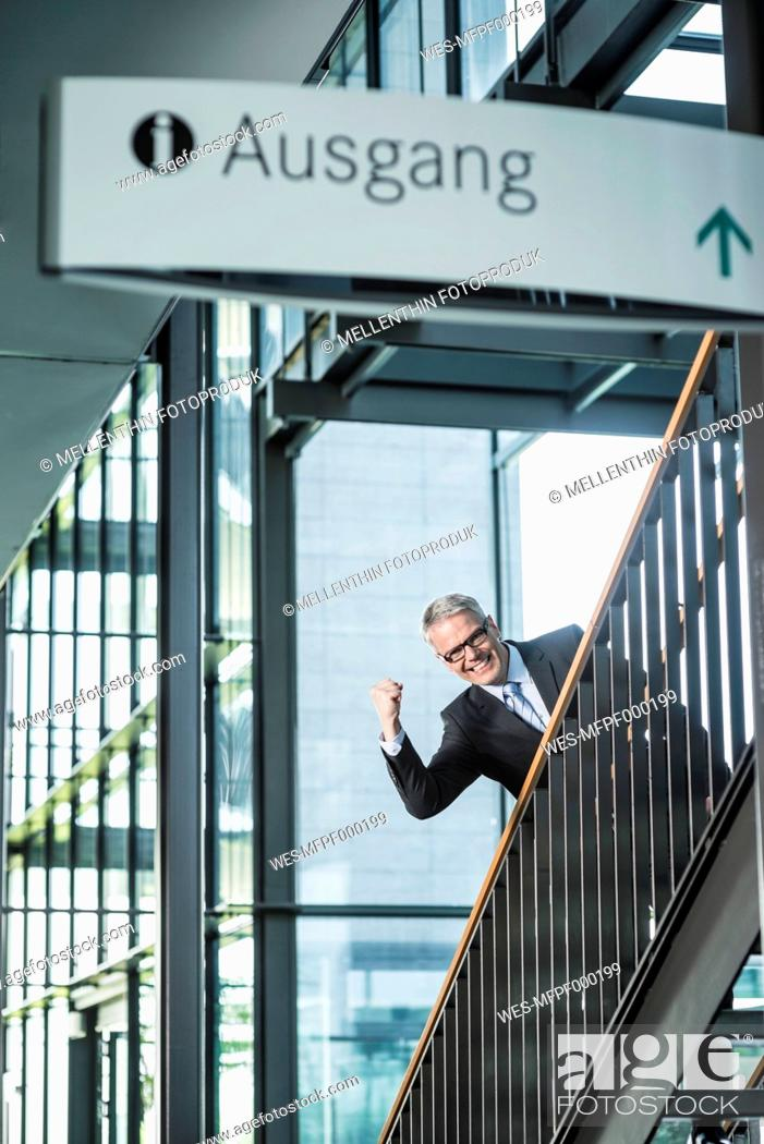 Stock Photo: Germany, Stuttgart, Businessman moving up on office staircase, portrait, smiling.