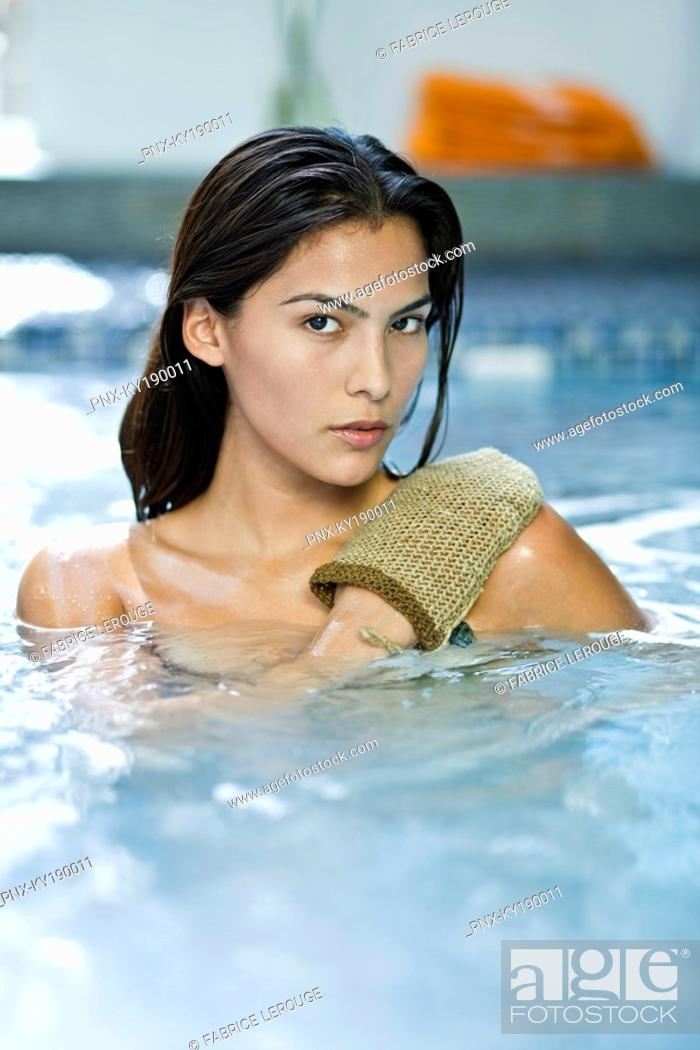 Stock Photo: Portrait of a woman using an exfoliation glove.