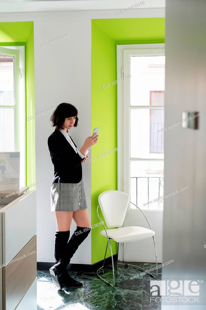 Stock Photo: Young female business creative looking at smartphone in office.