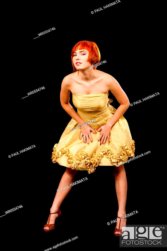 Imagen: Beautiful Caucasian redhead woman in yellow cocktail dress, isolated.