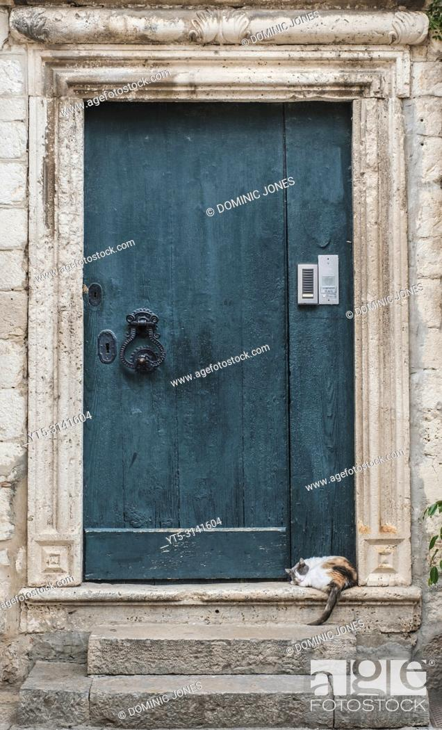 Stock Photo: A cat snoozes on a doorstep in the Old Town, Dubrovnik, Croatia, Europe.