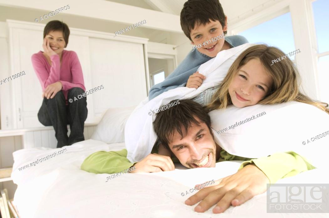 Stock Photo: Smiling couple and two children on bed.