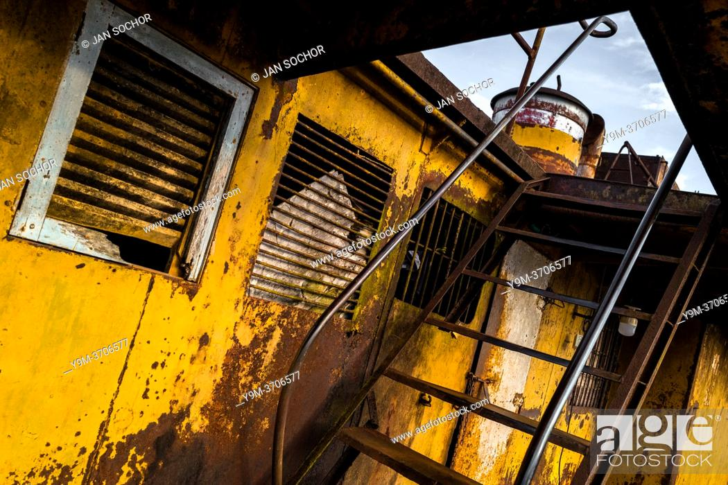 Stock Photo: A corroded stairs to the second deck is seen on an old gold dredge anchored in the Atrato river in Quibdó, Colombia. A gold dredge is a mining machine employing.